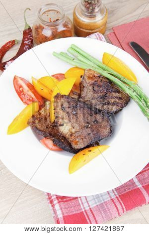 meat food : grilled beef fillet with mango tomatoes and asparagus , served on white dish on red table map over wooden table
