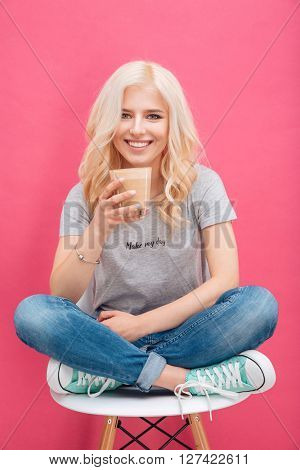 Smiling young woman drinking cappuccino and looking at camera over pink backgroud