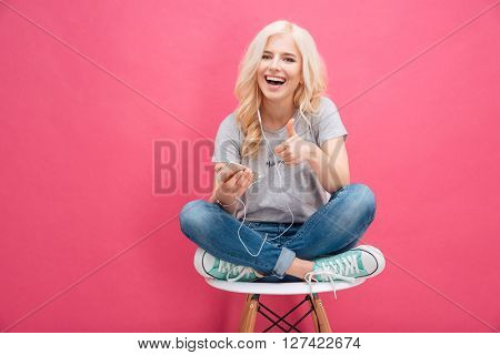 Cheerful woman listening music in headphones and showing thumb up over pink background
