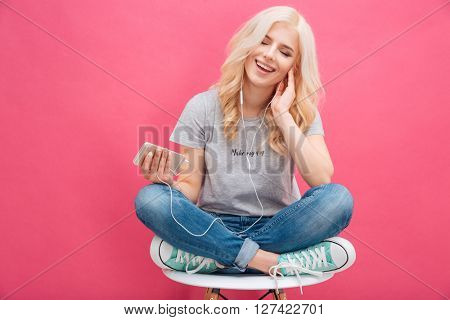 Cheerful blonde woman sitting on the chair and listening music in headhpones over pink background