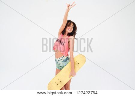 Charming woman holding skateboard and showing peace sign isolated on a white background