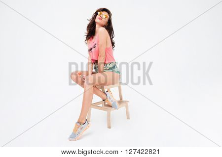 Charming woman in sunglasses and candy sitting on the chair isolated on a white background