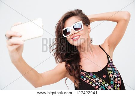 Smiling woman in sunglasses making selfie photo on smartphone isolated on a white background