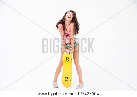 Laughign sexy woman posing with skateboard isolated on a white background