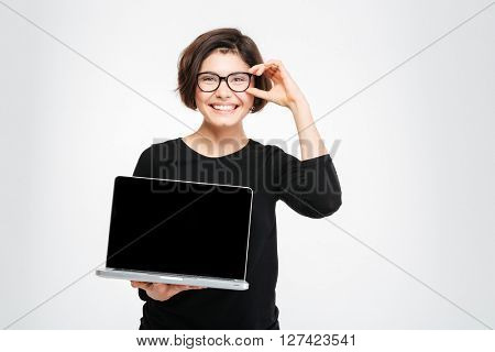 Smiling woman showing blank laptop computer screen isolated on a white backgroudn