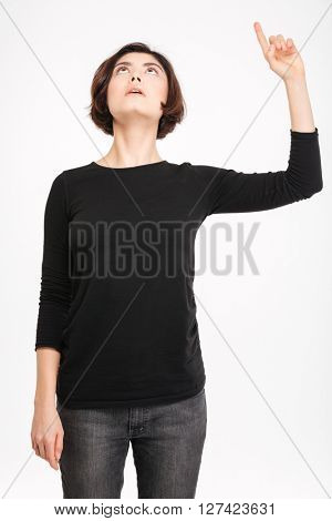 Young woman pointing finger up isolated on a white background