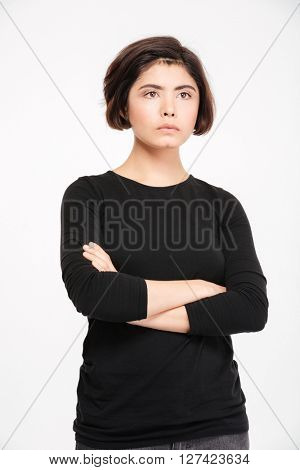 Pensive young woman standing with arms folded isolated on a white background