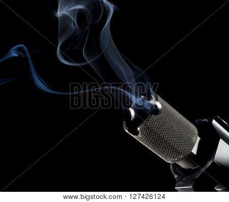 Barrel on a firearm smoking after a shot on a black background