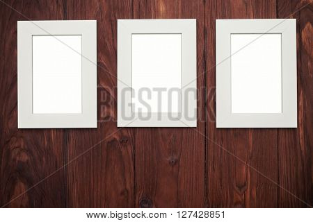 Three vertical empty beige photo frames in a row on brown wood