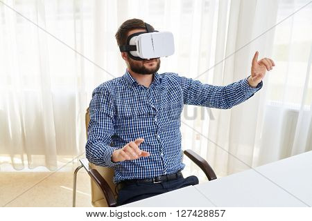 Young man is framing something with his fingers while using virtual reality glasses