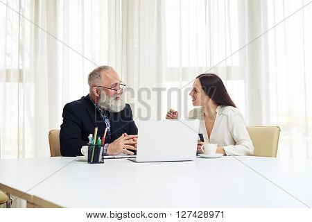 Young business woman and businessman sitting at the table and discussing new projects