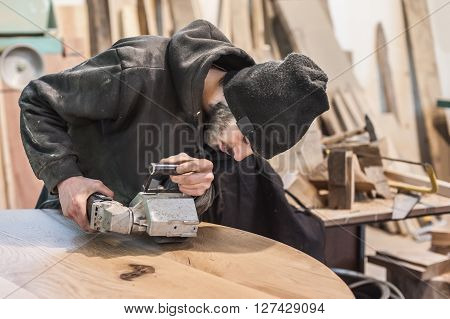 Man doing woodwork in carpentry. Carpenter work on wood plank in workshop