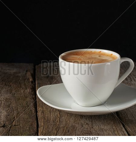 cup of coffee with thick of crema on wooden table on black background close up with copy space