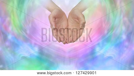 Female cupped hands emerging from a wispy pastel colored background with plenty of copy space