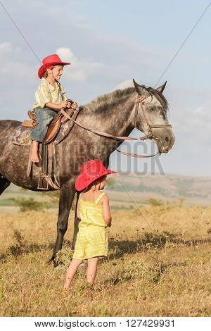 two young happy kids riding a horse on farm, outdoor portrait on rural background