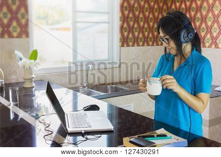Relaxing Life Style Asian Girl Drinking Hot Drink And Watching Media On Internet With Notebook And C