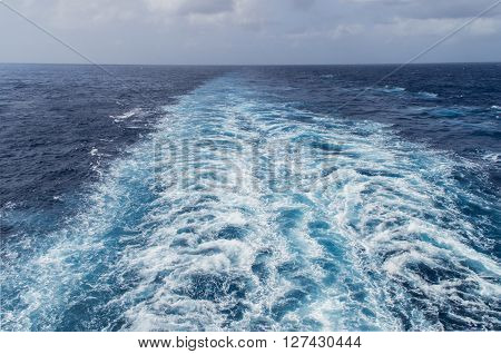 The engines of a cruise ship push out a hughe fantail of waves in the Caribean Sea