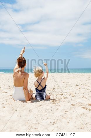 Seen From Behind Mother And Child Pointing Up At Sandy Beach