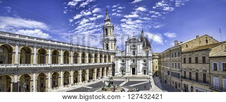 Loreto,Italy - June 20, 2015: Tourists stand in the Loreto main plaza named Piazza della Madonna. They sit near the Maggiore fountain wating to visit the Shrine of the Holy House.