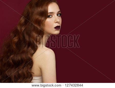 Beautiful Redhead girl with a perfectly curls hair and classic make-up. Beauty face. Picture taken in the studio.