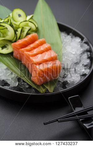 Japanese Cuisine. Salmon Sashimi On Ice Over Black Background.