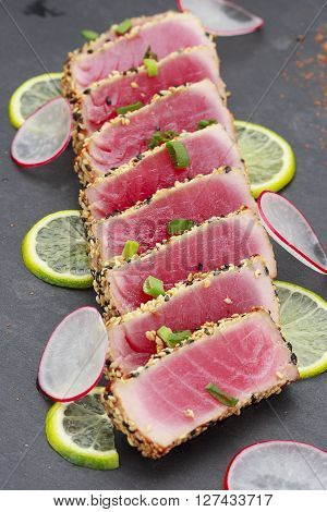 Tuna Fillet With Sesame Decorated With Limon And Vegetables On A Stone Plate.