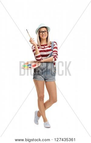Full length vertical shot of a young beautiful woman holding a paintbrush and a color palette isolated on white background