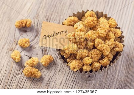 Mulberries in a bowl with a tag