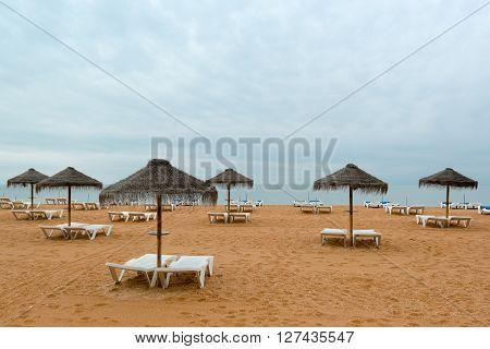 Lonely beach with chairs and umbrellas at the end of the vacation period