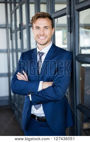 Portrait of businessman standing with arms crossed and smiling in office