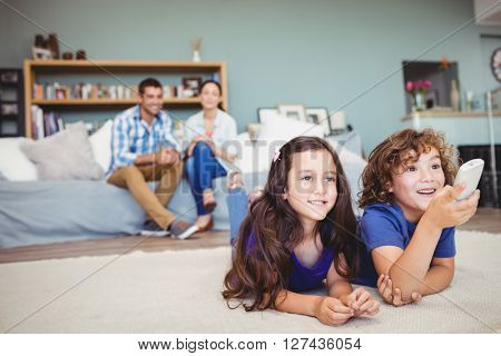 Close-up of happy children with remote while parents in background at home