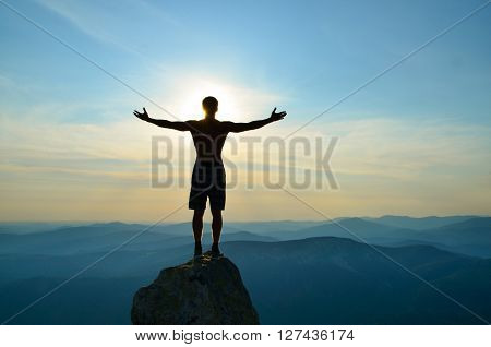 Man standing on top of a mountain with open hands to the sides