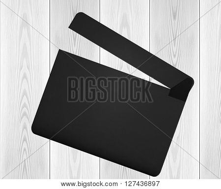 Black movie clapperboard on the wooden background