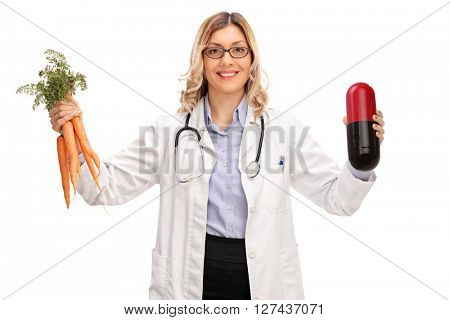 Young female doctor holding a huge pill and a bunch of carrots isolated on white background