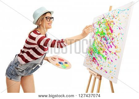 Young woman painting on a canvas with a lot of different colors isolated on white background