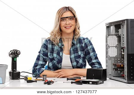 Female PC technician posing seated at a table with a bunch of tools on it isolated on white background