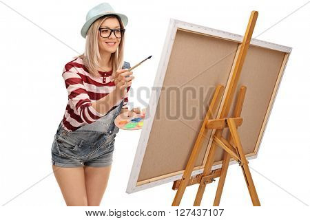 Studio shot of a young woman painting on a canvas with a paintbrush isolated on white background