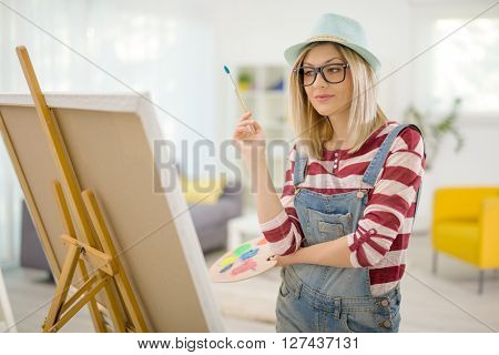 Young woman drawing on canvas and looking at the painting at home