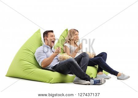 Joyful man and woman eating popcorn seated on beanbags and watching something isolated on white background