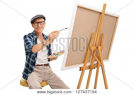 Studio shot of a senior artist painting on a canvas and looking at the camera isolated on white background
