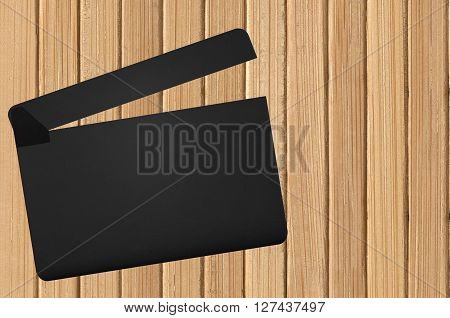 Black movie clapper on the wooden background