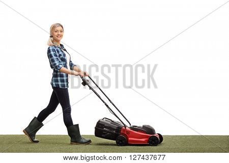 Young woman mowing a lawn with a lawnmower and looking at the camera isolated on white background