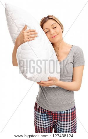 Vertical shot of a young blond woman hugging a pillow and sleeping isolated on white background