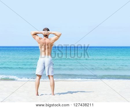 Young, fit and handsome man with athletic and muscled body standing on a summer beach
