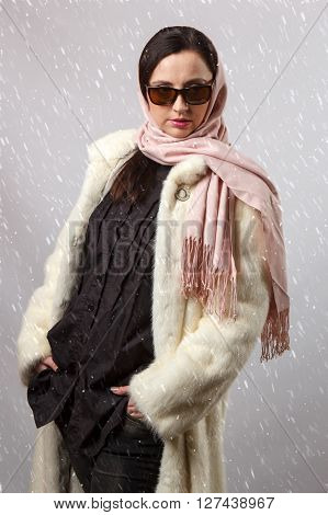 Portrait of glamor woman in glasses and headscarf with snow