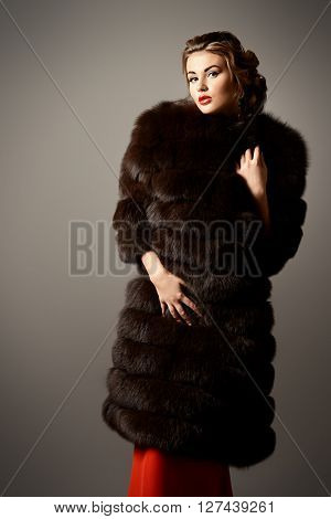 Portrait of a beautiful woman in red dress and luxurious fur coat. Luxury, rich lifestyle. Fashion shot.