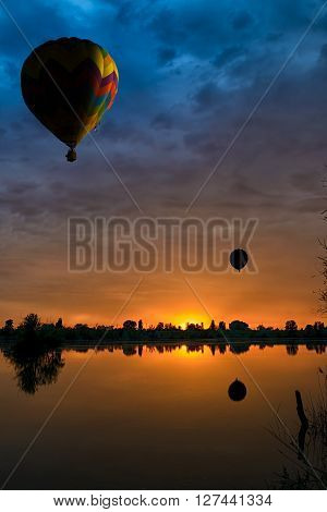 balloons in the sky at sunset over the lake