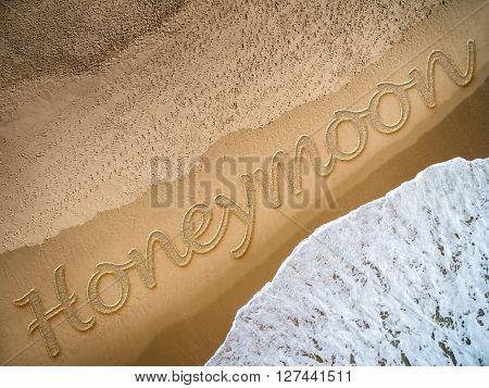 Honeymoon written on the beach