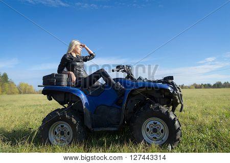 Elegant woman riding extreme quadrocycle ATV on a meadow