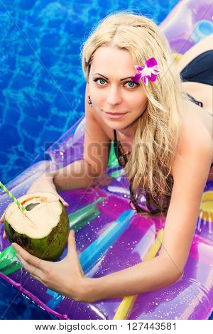 Young Pretty Blonde Woman On Air Mattress In Swimming Pool With Coconut Coctail Drink